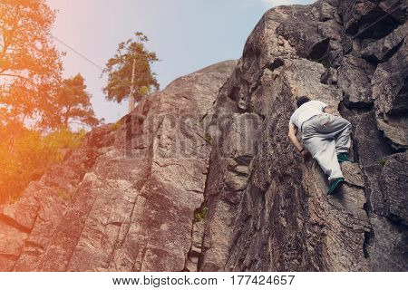 Young risky man passing over danger mountain without safety rope and harness