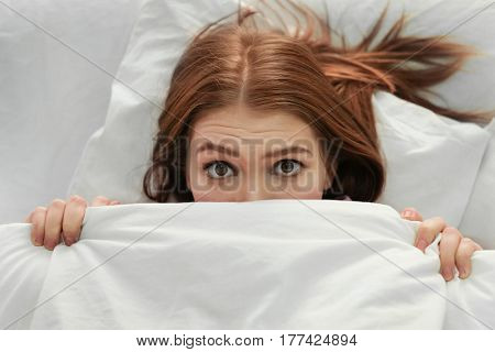 Young woman with sleep disorder lying in bed at home