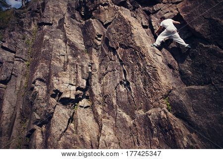 Young risky man climbing over danger mountain without rope