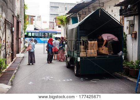 Penang, Malaysia - September 15, 2014: A working man unloads boxes from a lorry