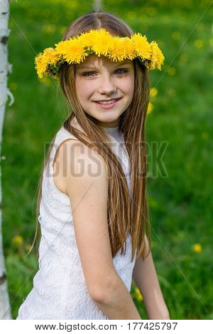 Girl Are Sitting In The Grass With Wreath Of Dandelions On Her Head