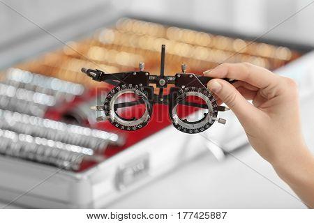 Doctor hand holding frame for trial lenses