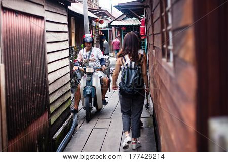 Penang, Malaysia - October 15, 2014: Architecture narrow streets with people on motocycle. Dirty moldy humidity cityscape