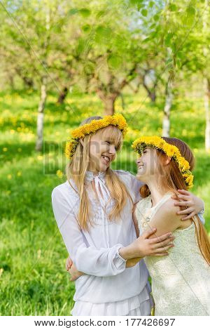 Girlfriends Are Standing With Wreaths Of Dandelions On Their Heads