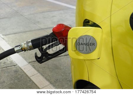 Nozzle fuel Gasohol 95 serving in to small car yellow color The door cover has sticker sign silver danger word.