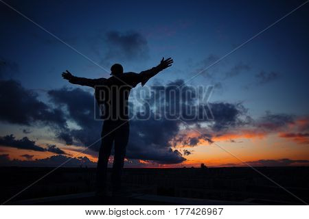 Silhouette of a young active man with outspread hands standing on top of the roof in the city at sunset