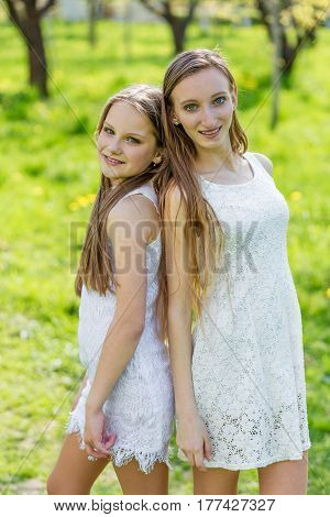 Two Beautiful Young Girls In White Dresses In Summer