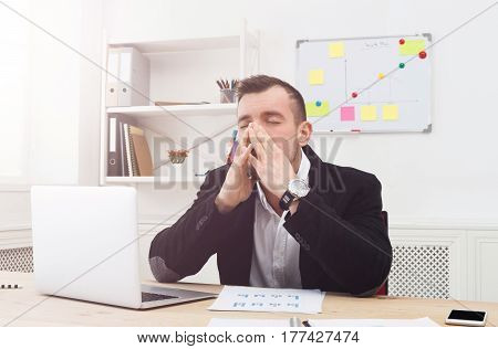 Young stressed, depressed and unhappy businessman with laptop in modern white office interior. Handsome man employee at work with computer, job problems concept. Lifestyle portrait