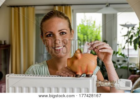 a young woman with a radiator and a piggy bank. symbol photo for saving energy and heating