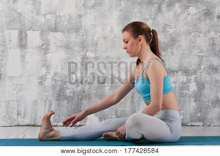 Young caucasian woman practicing yoga indoors. Fit healthy girl in sportswear sitting on blue mat against grey wall.