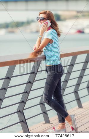 Girl using cellphone on the pier near the river.