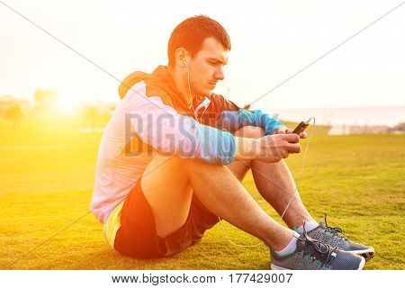 sportsman sitting on the grass in the park and touching his phone