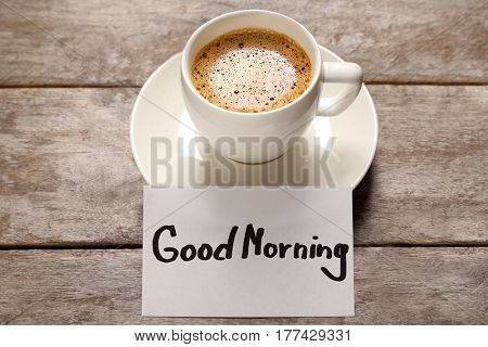 Cup of coffee and GOOD MORNING greeting note on wooden background