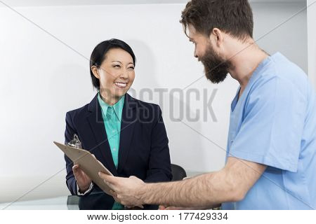 Receptionist And Doctor Discussing Over Clipboard