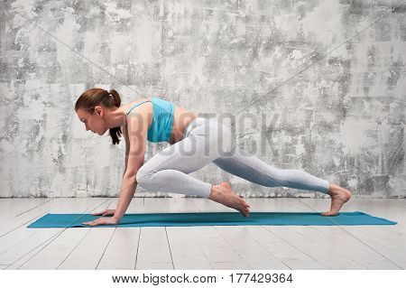 Girl wearing colorful sportswear practicing yoga indoors. Fit sporty woman exercising on blue mat.