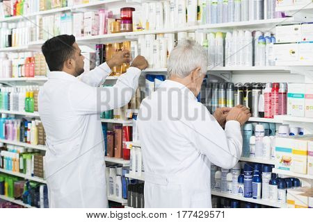 Multiethnic Chemists Arranging Stock On Shelves