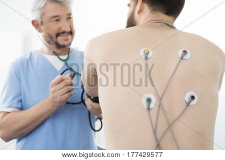 Doctor Examining Patient With Electrodes Attached On Back In Hos