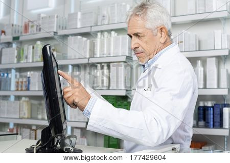 Male Pharmacist Touching Monitor Screen In Pharmacy