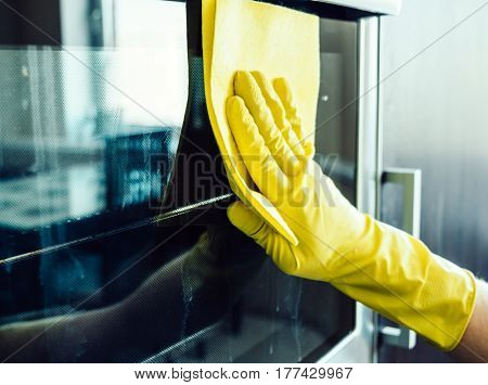 Man's Hand Cleaning The Kitchen Oven