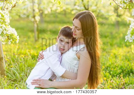 Mama Gently Hugs Her Son In The Rays Of The Setting Sun