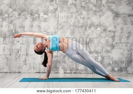 Sporty young woman doing yoga side plank position indoors. Beautiful fit girl exercising on blue mat against grey wall.