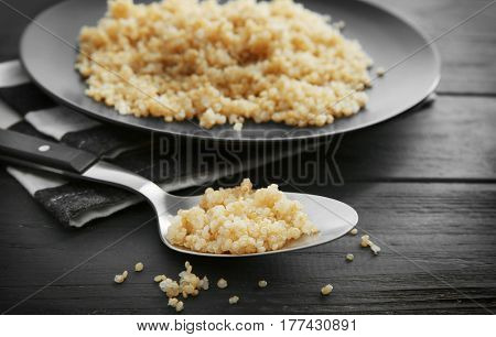 Spoon with boiled sprouted organic quinoa grains on wooden background