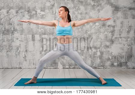 Young attractive woman wearing sportswear doing Yoga Warrior Pose. Fit girl exercising on blue mat against grey wall indoors.