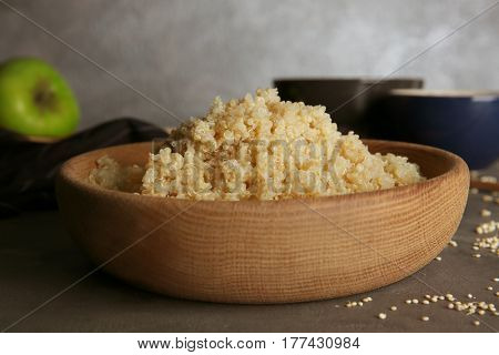 Wooden bowl with boiled sprouted organic white quinoa grains on kitchen table