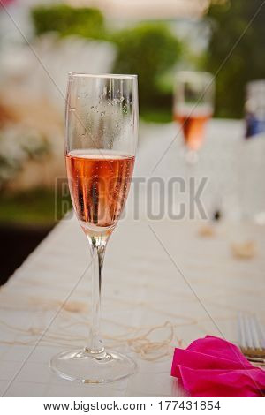 white table decorated with pink napkin and a glass of sparkling wine. Champagne for birthday