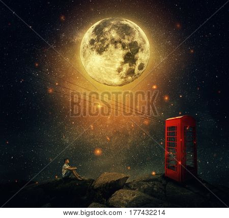 Imaginary view as a young man sitting on the cliff wait for someone to call him at the phone booth (box). Full moon night with a starry sky background. Loyalty and hard determination concept.