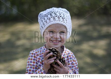 girl in knitted white cap is collecting cones in the forest and laughing