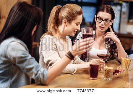After workday. Delighted blonde sitting in semi position between two friends putting arms on the table while listening to her colleague
