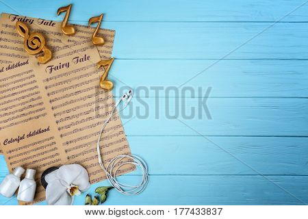 Composition of music sheets and spa supplies on wooden background