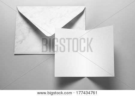 Blank card and envelope over grey background with shadow