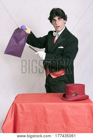 Mature magician performing magic tricks, taken on a white background