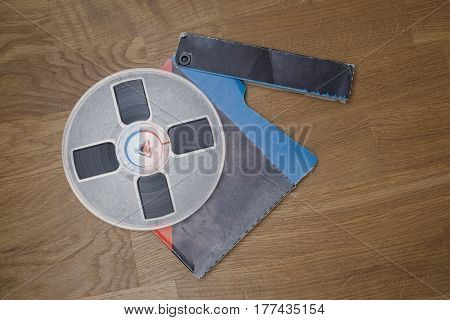 Vintage magnetic audio tape, reel to reel type, paper box on the grunge wooden floor