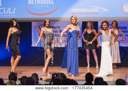MAASTRICHT THE NETHERLANDS - OCTOBER 25 2015: Female figure models in evening dress show their best physique in championship on stage at the World Grandprix Bodybuilding and Fitness of the WBBF-WFF