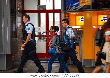 Munich,Germany-September 19,2015: Police officers escort an arriving migrant woman at Munich Central Station