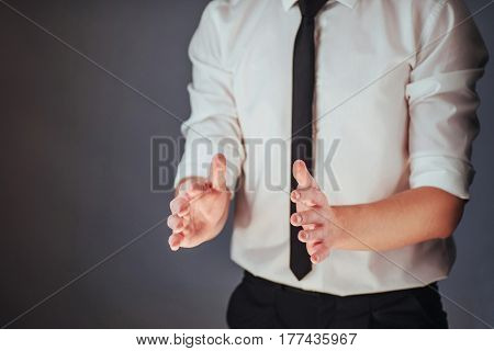 The Young Businessman In A Suit Shows His Hand On A Dark Background Isolated