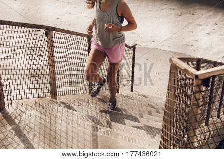 Cropped shot of fit young woman climbing up the steps on beach. Female runner exercising on staircase on sea shore.