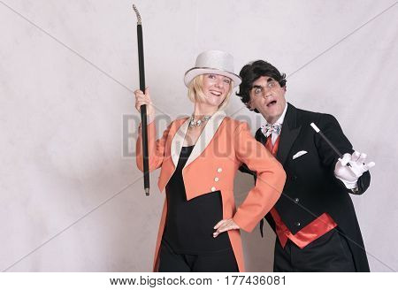Magician and assistant performing magic tricks, taken on a white background