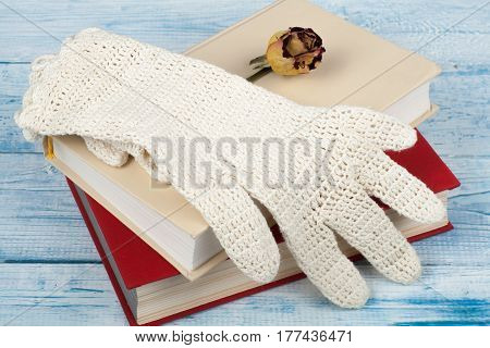 Open book hardback books on wooden table rose and white gloves knitted crochet Back to school. Copy space for text