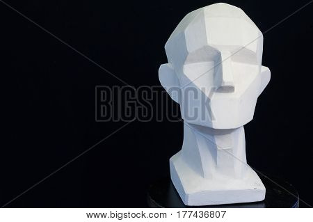 plaster bust of the person on a black background in style a cubism. art concept. empty space for the text. fullface of the person. model of the head of the human.