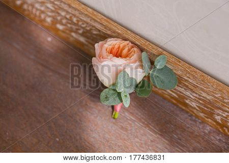 Wedding decorating boutonniere of pink rose ang green petal, on wooden brown background