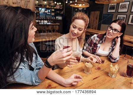 Best wishes. Positive delighted blonde sitting between her best friends holding glass in right hand while smiling and looking enigmatically