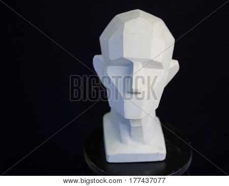 plaster bust of the person on a black background in style a cubism. concept of the person. empty space for the text. fullface of the person. model of the head of the human.