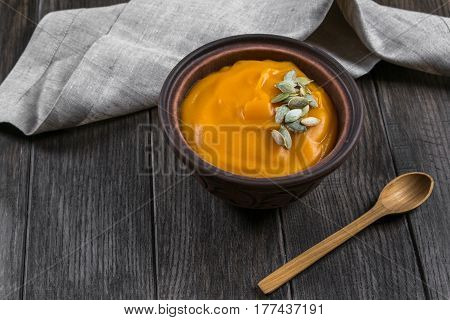Pumpkin cream soup with seeds in a clay bowl on dark wooden  table