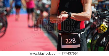 Triathlete checks his time as he runs to the swim-to-bike transition area