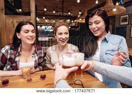Here I am. Positive delighted females wearing casual clothes offering three bocals of beer while sitting in pub