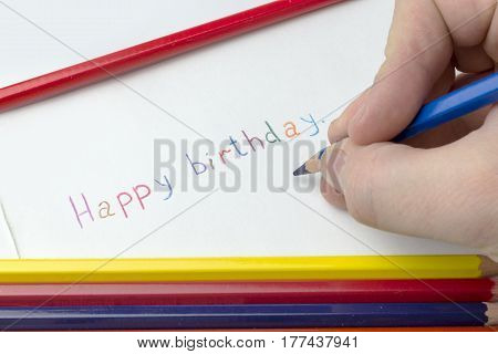 The hand with a pencil wrote on paper with a birthday.
